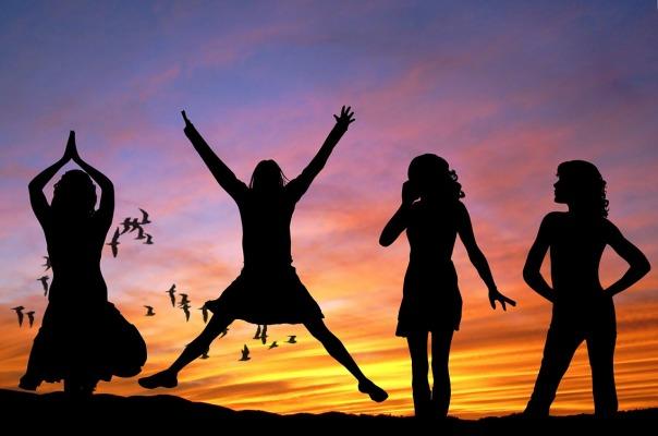 Four women celebrating women's day in the beautiful sunset